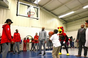 student shoots basketball while Hawks players watch