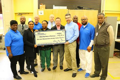 school and company leaders hold large check