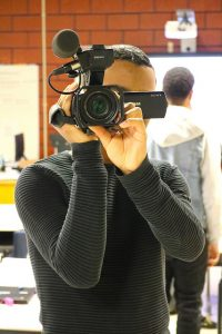 male student holds video camera