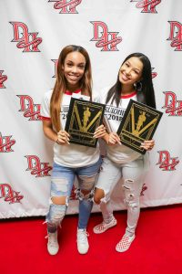 two female students hold yearbooks on red carpet