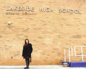 Ozbarlas stands under Lakeside High sign