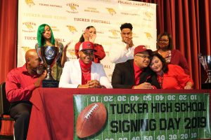 tucker player smiles with family surrounding