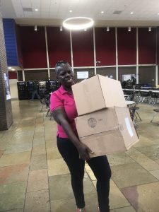 woman in pink shirt holds two boxes