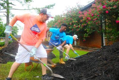 three men shovel mulch