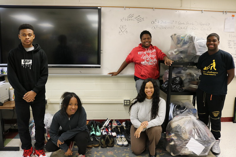 students stand in room with donated shoes